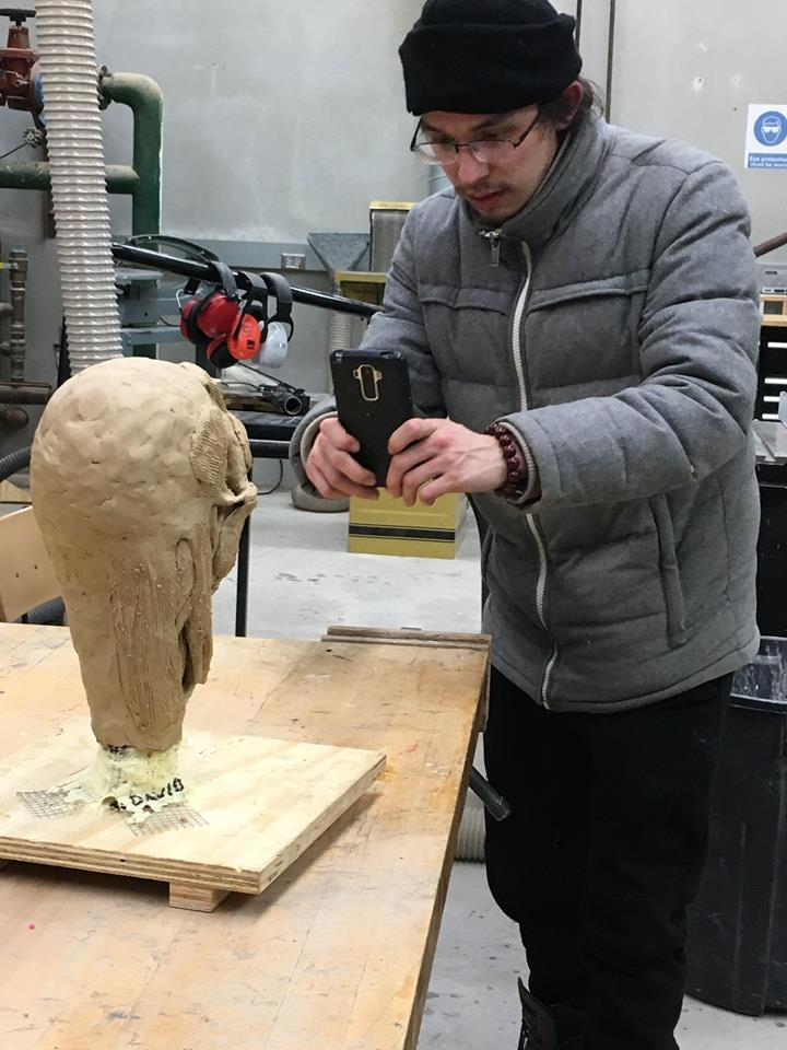 student photographing his figurative sculpture