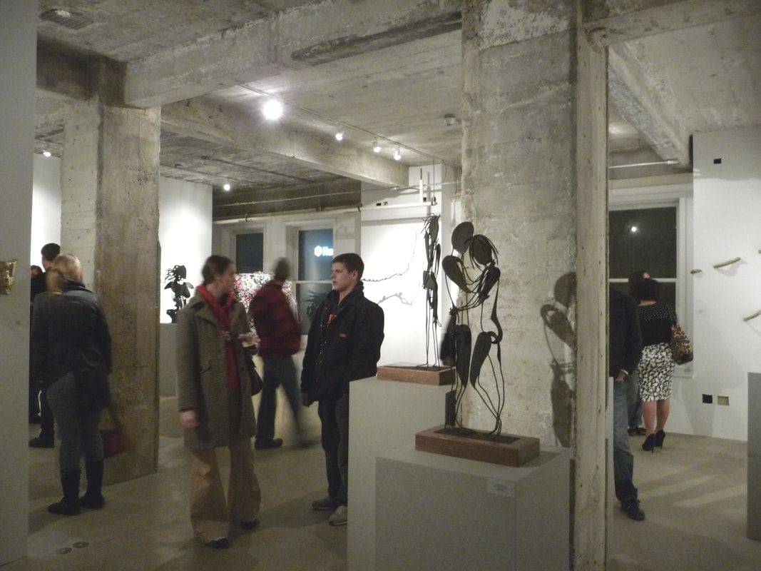 Gallery attendees viewing sculpture